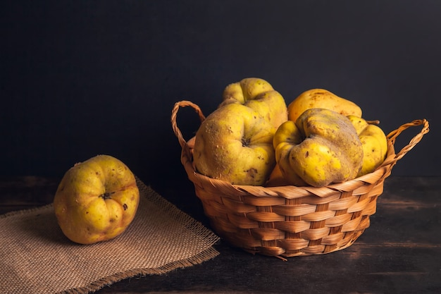 Natural quince fruit with defects in a basket on a jute napkin and a dark wooden background.