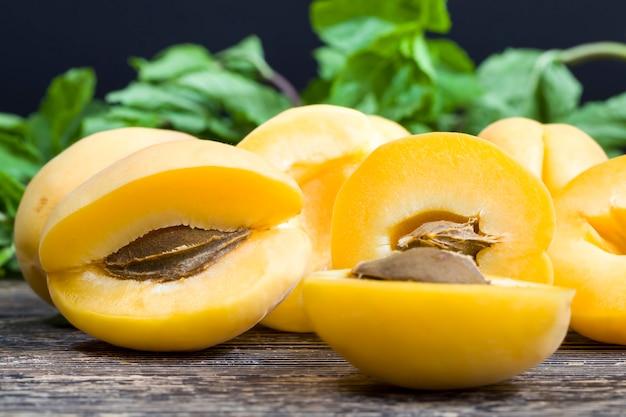 調理中に自然に熟したおいしいスライスしたオレンジ色のアプリコットは、新鮮なアプリコットフルーツのクローズアップのグループに横たわっています