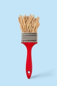 パステルブルーの背景に赤いペイントブラシで自然に熟した小麦、コピースペース。夏の収穫風景を描く。
