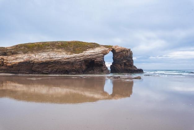 ルーゴ、ガリシア、スペインの大聖堂のビーチでの自然の岩のアーチ。