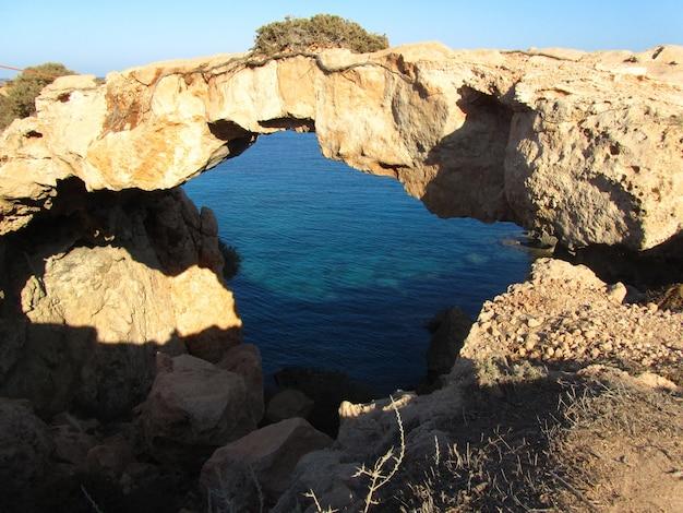 키프로스의 케이프 그레코 국립 삼림 공원에서 바다로 둘러싸인 자연 바위 아치