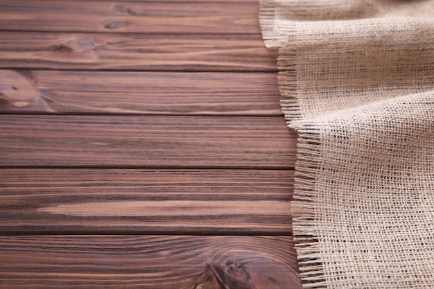 Natural sackcloth on brown wooden background. canvas on brown wooden table