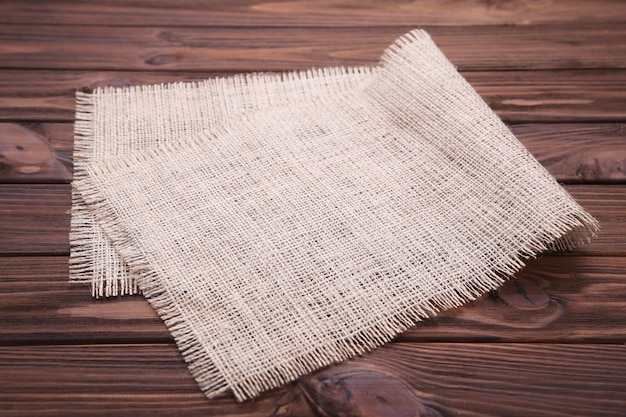 Natural sackcloth on brown wooden background.