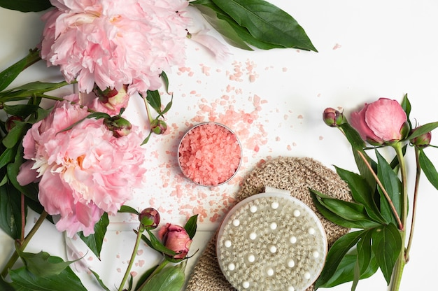 Natural salt for bath with dry massage brush and peony flowers