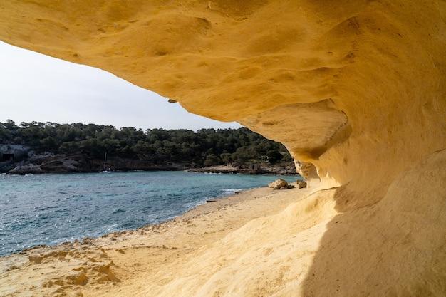 穏やかな海と人けのないビーチの自然の砂の洞窟