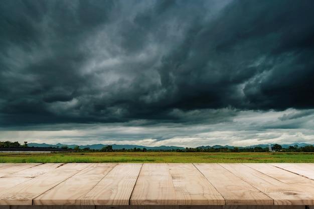 自然の風光明媚な美しいフィールド嵐雲と製品の表示とモンタージュのための空の木製テーブル。