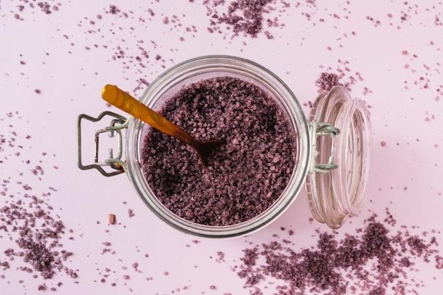 Натуральный скраб в открытом стакане с деревянной ложкой на розовом фоне