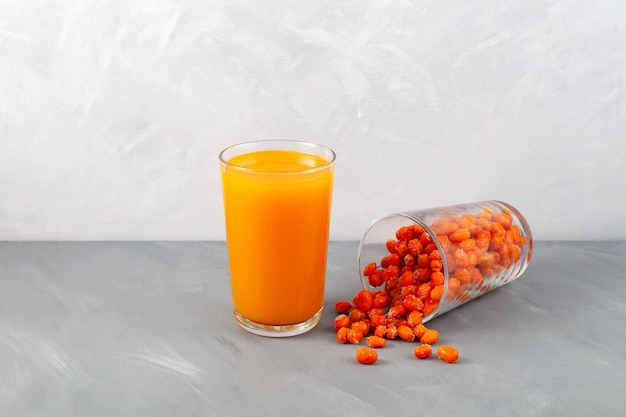 Natural sea buckthorn juice and frozen sea buckthorn berries spilled out of glass on the table