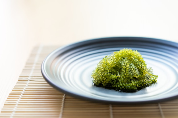 Natural sea grapes close up served in the luxury black stone plate in the japanese restaurant.  healthy and famous sea food.
