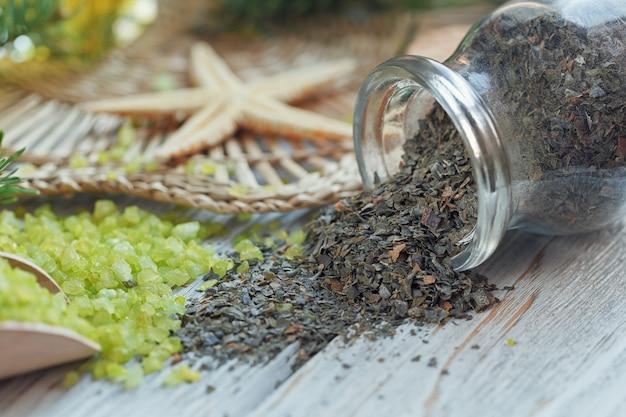 白い木の上に松と海藻の枝が付いた天然の海塩と手作り石鹸。