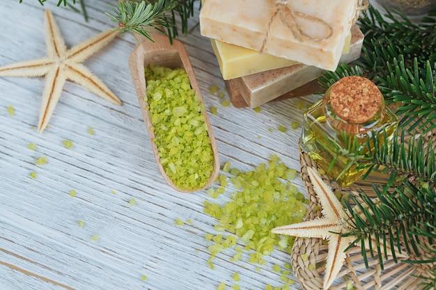 白い木の上に松の枝が付いた天然の海塩と手作り石鹸。