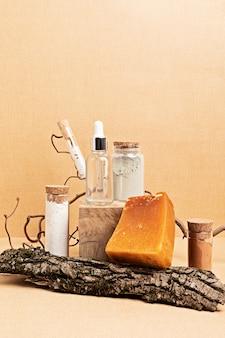 천연 세럼, 드라이 비누, 클레이 마스크가 나무 조각으로 장식되어 있습니다. 유기농 친환경 스파 뷰티 제품을 중성 색상 자연 환경에서 소개