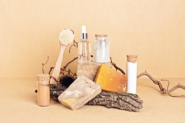 Natural serum, dry soap and clay masks displayed with pieces of wood. presentation of organic eco friendly spa beauty products in neutral colors nature environment