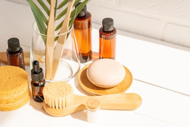 天然美容液、ドライソープ、スポンジ、テーブルに天然毛をつけたフェイスマッサージブラシ。ニュートラルカラーの自然環境におけるオーガニックの環境にやさしいスパ美容製品のプレゼンテーション。
