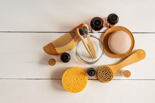 天然美容液、ドライソープ、スポンジ、テーブルに天然毛をつけたフェイスマッサージブラシ。ニュートラルカラーの自然環境におけるオーガニックの環境にやさしいスパ美容製品のプレゼンテーション