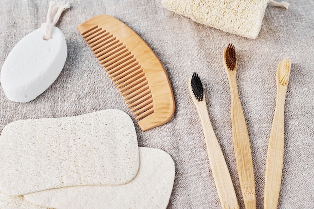 Natural set for bathing bamboo toothbrushes,  luffa spongle and wooden hairbrush on a linen background.