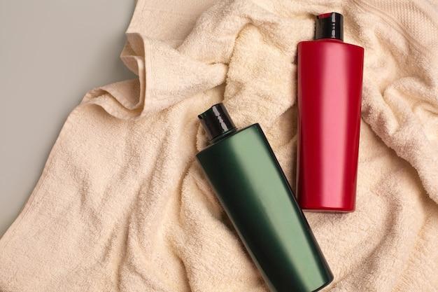 ナチュラルシャンプー、バスルームのしわくちゃのタオルの上に横たわる保湿コンディショナー。コピースペース