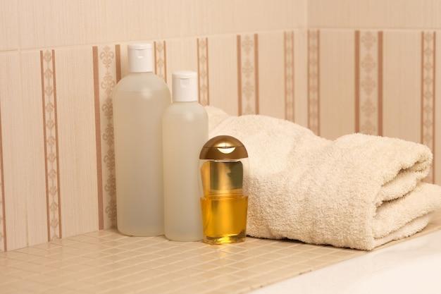 バスルームに天然シャンプー、シャワージェル、ヘアオイル、バスタオル。テキスト用のスペース
