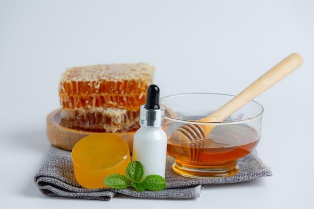 흰색 표면에 꿀과 벌집이 깔린 천연 스킨 케어 비누와 세럼.