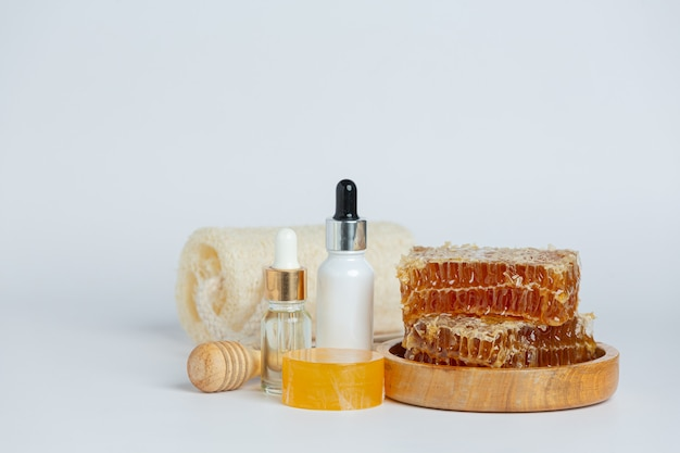 Natural skin care soap and serum with honey and honeycomb laid on white surface.