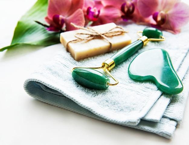 手作りの天然石鹸、翡翠のフェイスローラーとコットンタオルのクローズアップ、スパとスキンケアのコンセプト、天然のオーガニックウェルネス製品、ホームスパを備えた天然のスキンケアとスパ製品