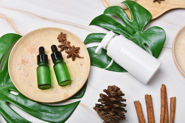 향신료 오일이 함유 된 천연 스킨 케어 미용 제품, 녹색 자연 잎으로 포장 된 화장품 펌프 병 용기, 유기농 스파 브랜딩 모형 용 빈 라벨, 허브 건강 피부 관리.
