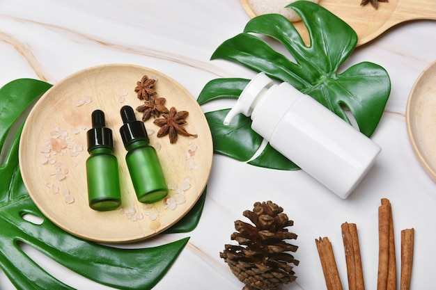 Natural skincare beauty product with spices oil, cosmetic pump bottle containers packaging with green nature leaves, blank label for organic spa branding mock-up,herbal healthy skin care.