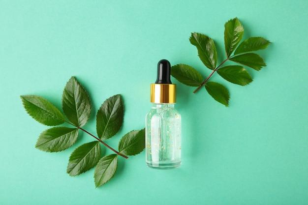 天然のスキンケアボトル容器と有機緑の葉、ミントの表面に実験用ガラス器具で花の成分