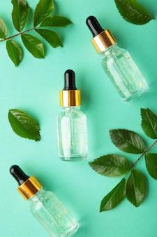 天然のスキンケアボトルの容器と有機緑の葉、ミントの表面に実験用ガラス器具で花の成分