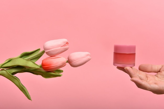 Natural skincare pink bottle, hand showing cosmetic containers packaging with tulip flower essence extract, organic beauty product concept.