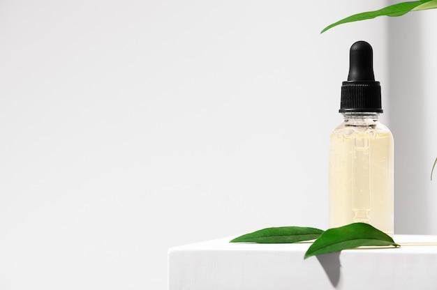 スポイト付きガラス瓶に入った天然スキンケア製品。女性の顔の皮膚のための血清。ハーブミネラル化粧品、白いスタンドにビタミンボディオイル。ピペット付きの透明パッケージ美容。スペースをコピーします。