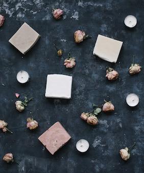 Натуральное мыло и розовые цветы на темной поверхности