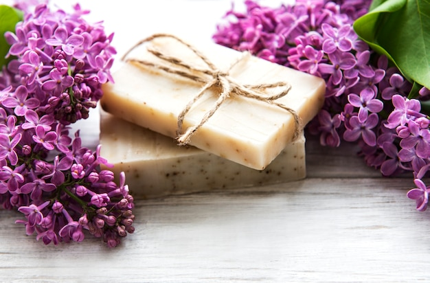 Natural soap and lilac flowers on a white wooden surface, top view