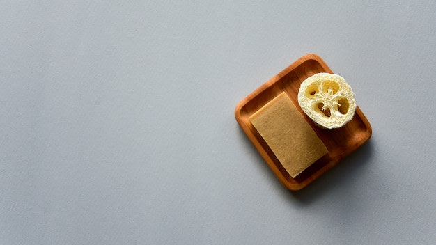 Natural soap and loofah bath sponge on a wooden plate. gray paper background. zero waste concept. top view.
