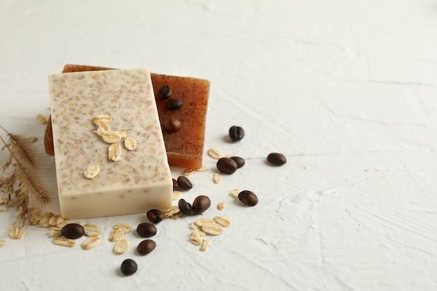 白いテーブルの上の天然石鹸、オート麦、コーヒーの種子