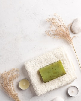 Natural soap with herbs and bath towel on a white stone background handmade natural spa products concept , copy space,