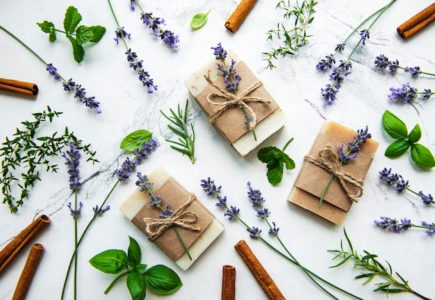 Natural soap with rosemary, thyme, lavender, mint on a white marble background