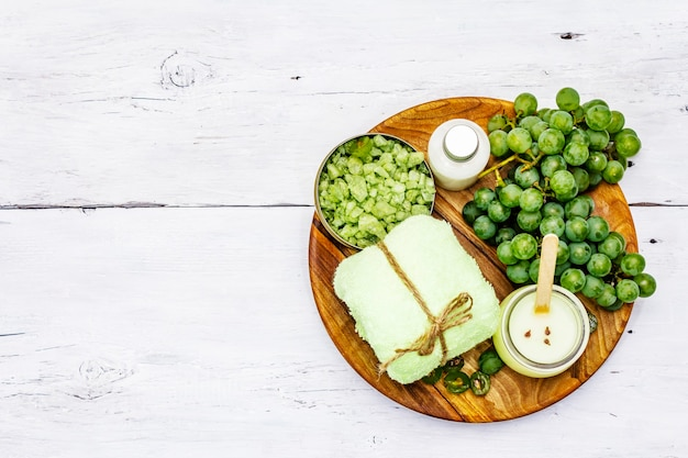 Natural spa accessories and green grapes placed on a wooden plate, top view