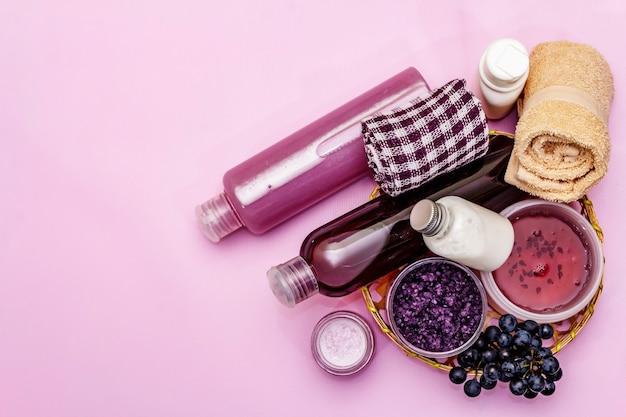 Натуральные спа-аксессуары со спелым виноградом. свежие ингредиенты для здорового и красивого ухода за собой. розовый фон, вид сверху
