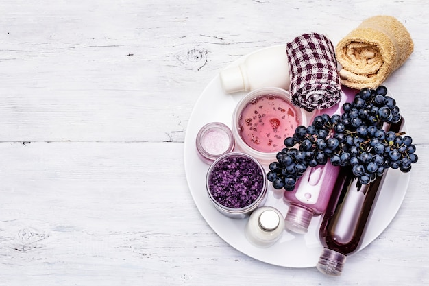 Natural spa accessories with ripe grapes. fresh ingredients for healthy and beauty self care. white wooden boards background, top view