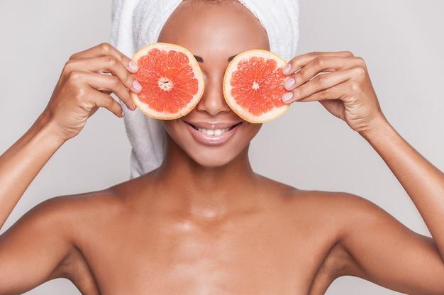 ナチュラルスパ。灰色の背景に孤立して立っている間彼女の目の前にオレンジの部分を保持している美しい若いアフリカ系アメリカ人の上半身裸の女性