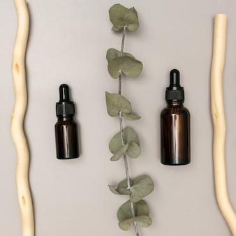 エッセンシャルオイルを使用したナチュラルスパのコンセプトで、明るい灰色の背景にユーカリの葉があります。有機化粧品、ウェルネス、美容トリートメント。クローズアップ、上面図。