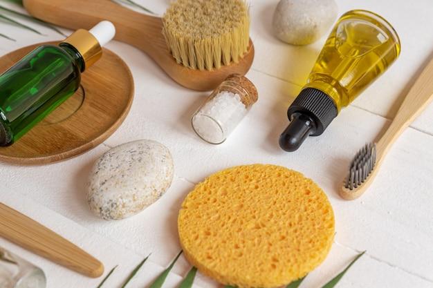 ナチュラルspa化粧品、エッセンシャルオイルのボトル、海塩、スポンジ、ブラシ、白い背景のマッサージツールを使用したコンポジション。ゼロウェイストコンセプト