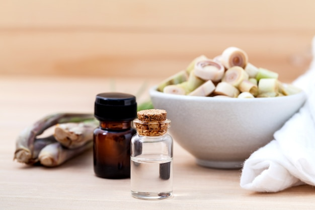 Natural spa ingredients lemongrass essential oil on wooden background.