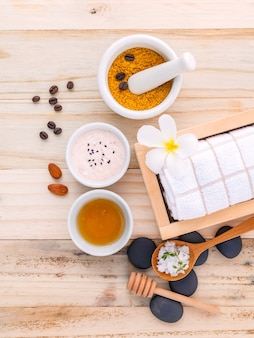 Natural spa ingredients and white mortar on wooden background .