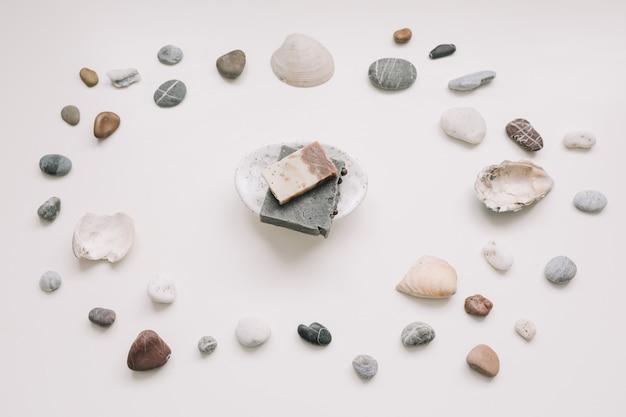 Натуральное спа органическое мыло на керамической мыльнице с морскими ракушками на белой поверхности