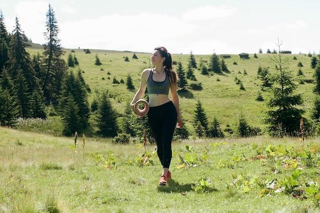 自然、スポーツ、健康、人々、ライフスタイルの概念-健康な若い独立した女性のヨガの実践者、瞑想を実践し、純粋さを見下ろす山の美しい穏やかな景色をポーズします