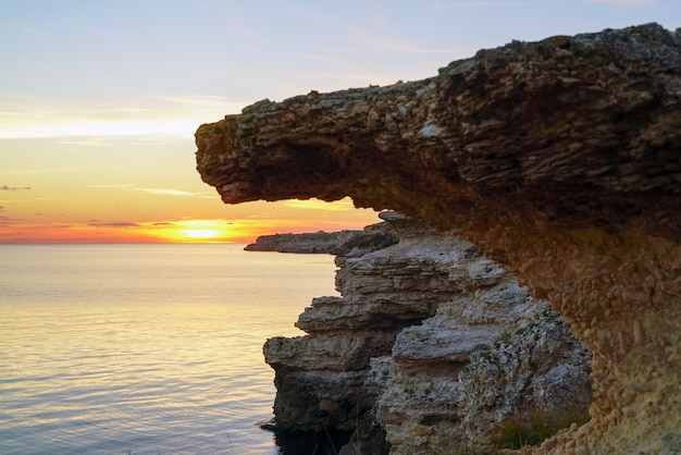 Natural stone rocks on the black sea at sunset.