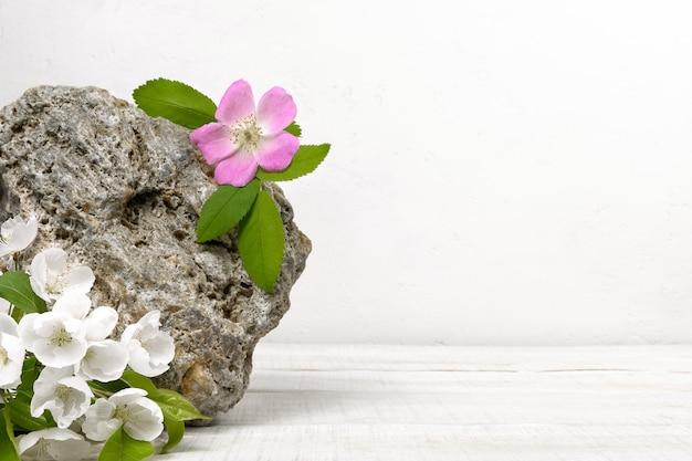 白い木製のテーブルに白とピンクの花と天然石