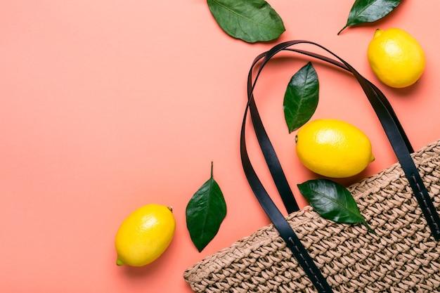 살아있는 산호 배경에 천연 밀짚 가방과 익은 레몬.
